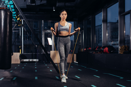 athletic girl exercising with jump rope at gym