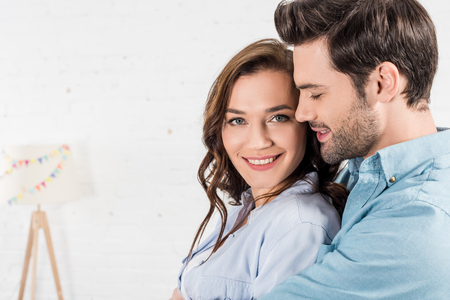Photo pour portrait of man embracing smiling woman at home - image libre de droit