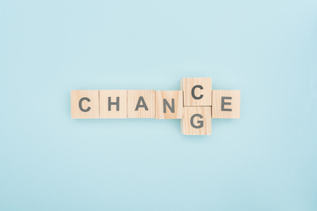 Photo pour top view switching chance to change lettering made of wooden blocks on blue background - image libre de droit