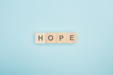 Photo for top view of hope lettering made of wooden cubes on blue background - Royalty Free Image