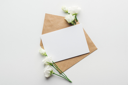 Photo pour top view of eustoma and envelope with empty card on grey background - image libre de droit