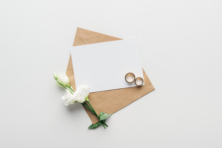 Photo pour top view of envelope with empty card, flowers and golden wedding rings on grey background - image libre de droit