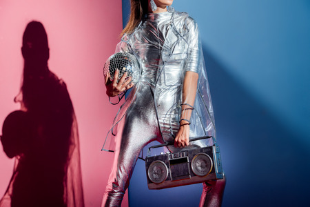 Photo for cropped view of fashionable woman in silver bodysuit and raincoat posing with boombox and disco ball on pink and blue background - Royalty Free Image