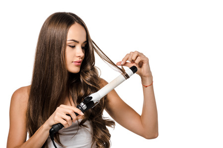 Photo pour beautiful girl with long brown hair using curling iron isolated on white - image libre de droit