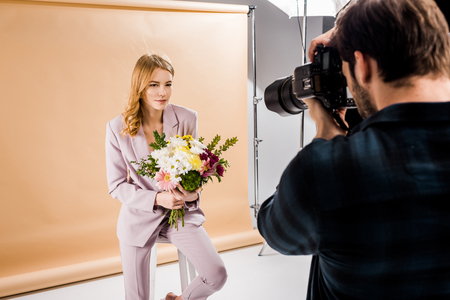 Photo for photographer shooting beautiful young woman posing with flowers in studio - Royalty Free Image