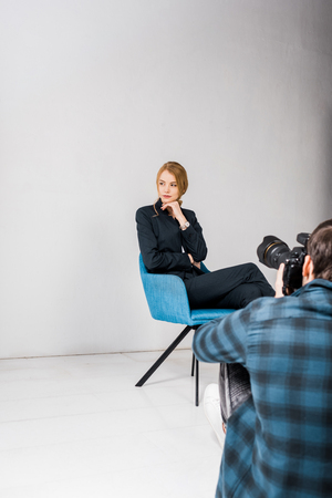 Photo for cropped shot of photographer shooting beautiful young woman in photo studio - Royalty Free Image