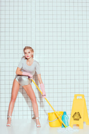 Photo pour beautiful housewife looking at camera while cleaning floor in bathroom - image libre de droit