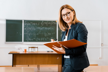Photo pour beautiful female teacher in formal wear writing in notebook and looking at camera in classroom - image libre de droit
