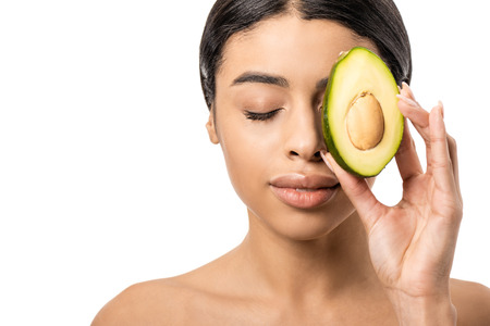 Foto de beautiful young african american woman holding half of avocado near face isolated on white - Imagen libre de derechos