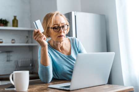 Photo pour senior woman in glasses holding credit card and using laptop while doing online shopping at home - image libre de droit