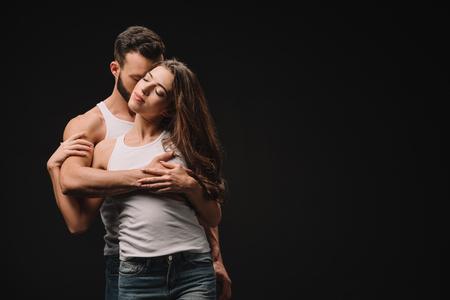 Foto de handsome man hugging and kissing young woman isolated on black - Imagen libre de derechos
