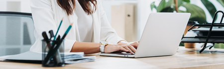 Foto de cropped view of businesswoman sitting at table with laptop and typing in office - Imagen libre de derechos