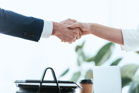Photo pour selective focus of woman and man shaking hands at office - image libre de droit