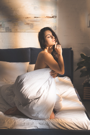 Foto de beautiful sensual woman covering body with duvet and sitting on bed at home - Imagen libre de derechos