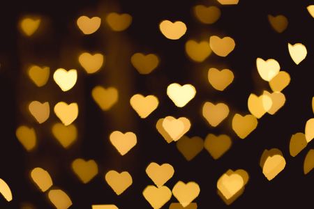 Foto per yellow heart shaped bokeh lights on black backdrop - Immagine Royalty Free