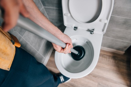 Foto de cropped shot of male plumber using plunger and cleaning toilet in bathroom - Imagen libre de derechos