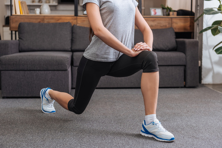 Foto de cropped view of sportswoman doing lunge exercise at home - Imagen libre de derechos