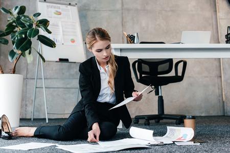 Foto de barefoot businesswoman sitting on floor and reading document - Imagen libre de derechos