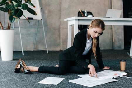 Foto de barefoot businesswoman sitting on floor near work-table and reading documents - Imagen libre de derechos