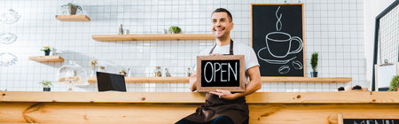 Photo pour handsome cashier in brown apron sitting on chair near wooden bar counter and holding chalkboard with open lettering in coffee house - image libre de droit