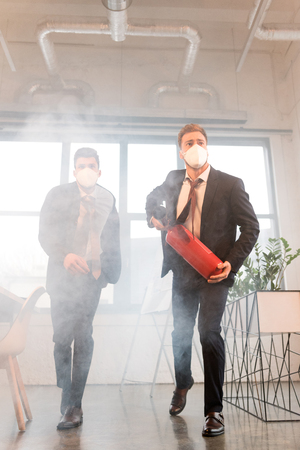 Photo for businessman in mask holding extinguisher near colleague while walking in office with smoke - Royalty Free Image