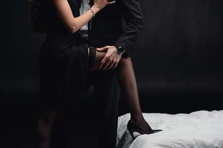 Foto de cropped view of man touching woman in stockings isolated on black - Imagen libre de derechos