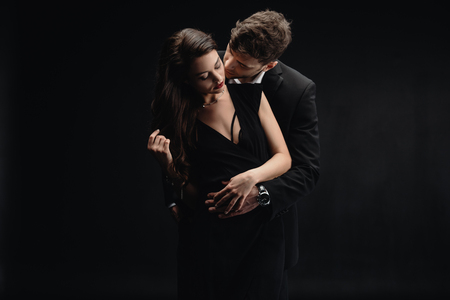 Foto per passionate young couple in formal wear kissing isolated on black - Immagine Royalty Free