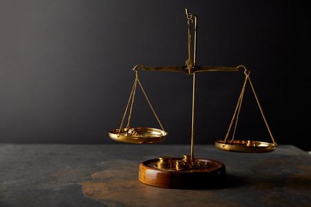 Foto de golden stones on scales on marble table and dark background - Imagen libre de derechos