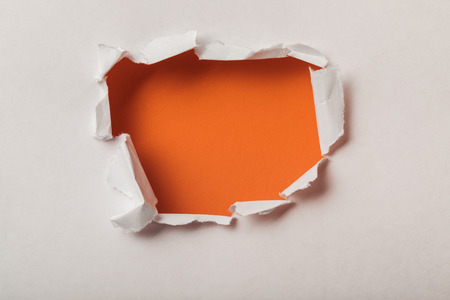 Foto de torn hole in sheet of paper on orange background - Imagen libre de derechos