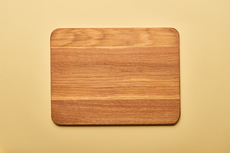 Foto de top view of empty wooden chopping board on yellow background - Imagen libre de derechos