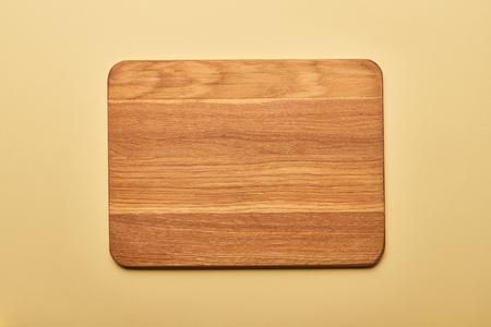 Foto de top view of empty wooden chopping board on yellow background - Imagen libre de derechos