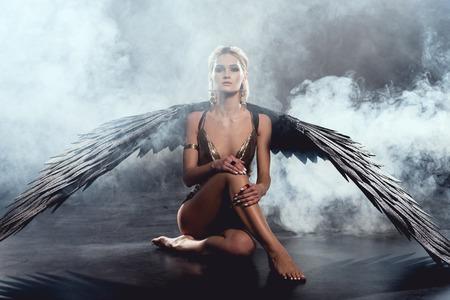 Foto de beautiful sexy woman with black angel wings sitting, looking at camera and posing on dark background - Imagen libre de derechos