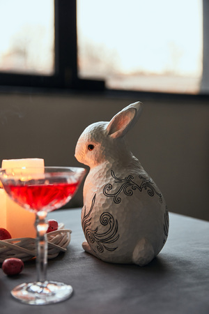 Photo for decorative bunnie, eggs, wine in crystal glass and burning candles on table at home - Royalty Free Image