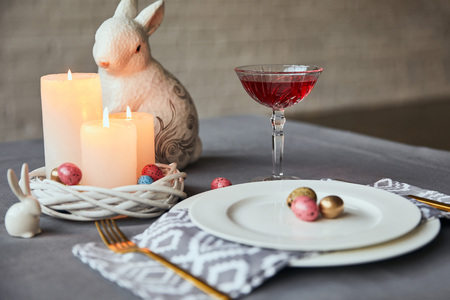 Photo for selective focus of plates with napkin, eggs and burning candles in basket, wine in crystal glass and decorative rabbit on table at home - Royalty Free Image