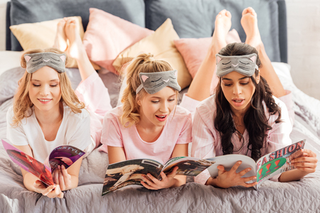 beautiful multicultural girls in sleeping masks reading magazines during pajama party
