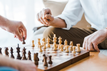 Photo pour selective focus of wooden chess board with seniors playing chess at home - image libre de droit