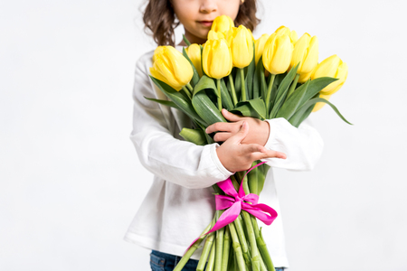 Photo for Partial view of kid holding bouquet of yellow tulips isolated on white - Royalty Free Image