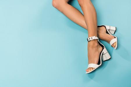 Foto de Partial view of woman in white sandals on blue background - Imagen libre de derechos