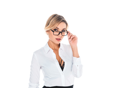 attractive blonde teacher in blouse with open neckline taking off glasses isolated on whiteの写真素材