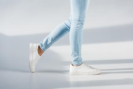 Foto de Partial view of woman in blue jeans and white shoes on grey background - Imagen libre de derechos