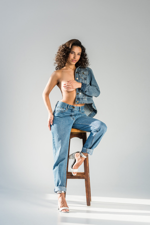 Attractive girl in jeans sitting on chair and covering breast with hand on grey background
