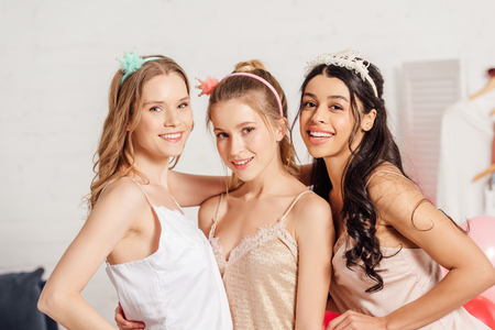 beautiful multicultural girls in headbands and nightwear smiling and looking at camera during pajama party