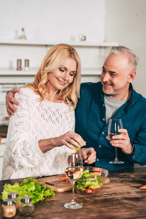 Foto de handsome man with glass of wine hugging attractive blonde wife holding green lettuce leaves - Imagen libre de derechos