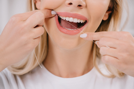 Photo pour cropped view of woman flossing teeth with dental floss - image libre de droit