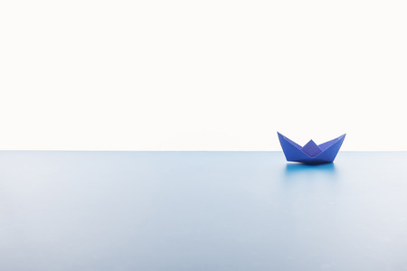 Foto de Blue paper boat on light surface on white background - Imagen libre de derechos