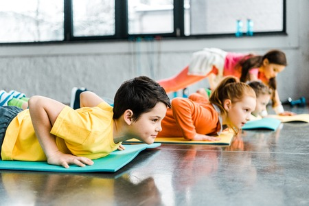 Preteen kids doing push-up exercise in gym