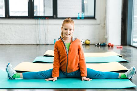 Foto de Cute kid doing twine on blue mat in gym - Imagen libre de derechos