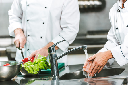 Foto de cropped view of female chef washing hands over sink while colleague cooking on background in restaurant kitchen - Imagen libre de derechos