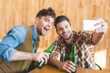 Photo pour handsome men holding glass bottles of beer and taking selfie - image libre de droit