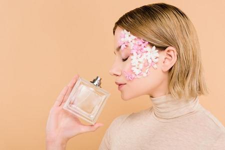 beautiful woman with flowers on face smelling perfume isolated on beige